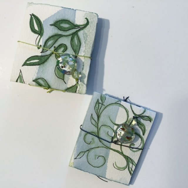 two tiny books, held shut by glass beads