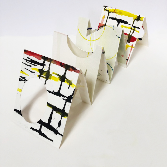 accordion folded watercolor paper with geometric shapes cut out, black yellow and red abstract marks painted